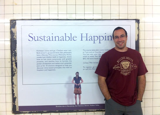 Ben Nadel in front of the Sustainable Happiness poster put up in the New York City subway system by the School of Practical Philosophy.